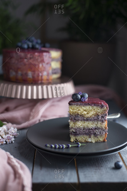 Layer cake with fresh blueberries, glazing, and lavender flowers being sliced and served