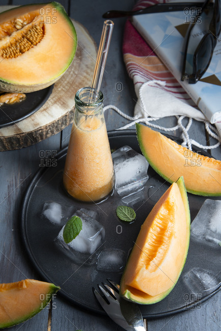Close up of cantaloupe melon fresh juice in a little glass bottle with ice cubes and mint