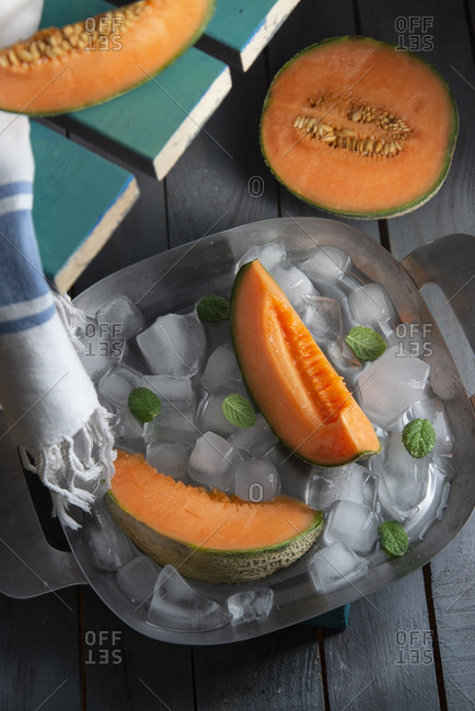 Cantaloupe melon slices with fresh mint on ice cubes