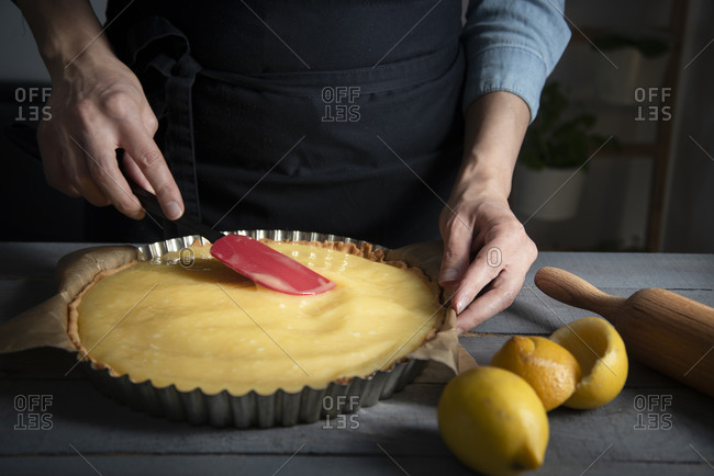 Hands smoothing out a lemon curd on a baked short crust pastry crust