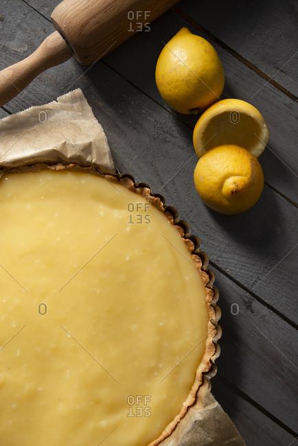 Overhead view of a lemon tart on wooden surface