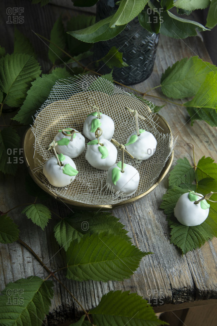 Matcha tea cake pops decorated and glazed with meringue on a wooden background