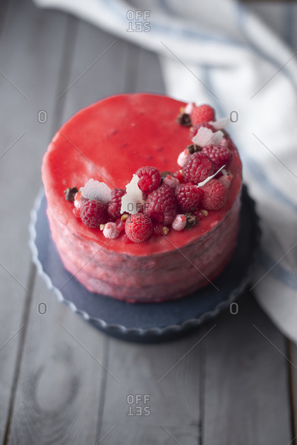 Red glazed raspberry layer cake on a wooden table