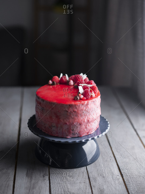 Red glazed raspberry layer cake on a cake stand on a wooden table