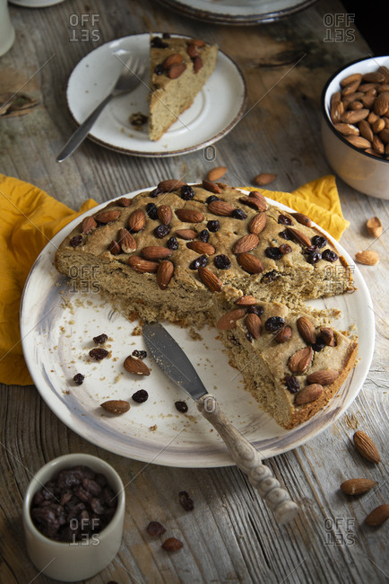 Overhead view of baked sorghum cake with almond and raisin being served
