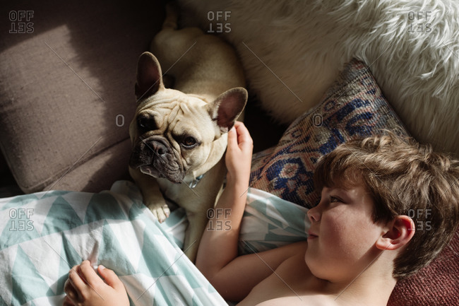 Young boy resting on sofa with his dog