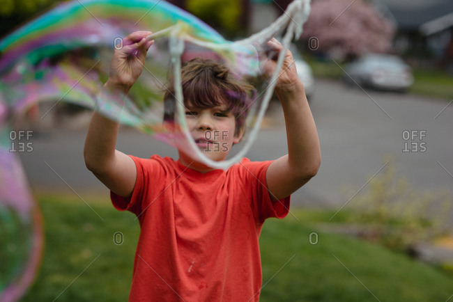 Boy playing with a large bubble wand