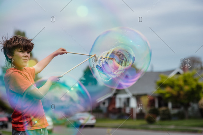 Young boy playing with a large bubble wand in front yard