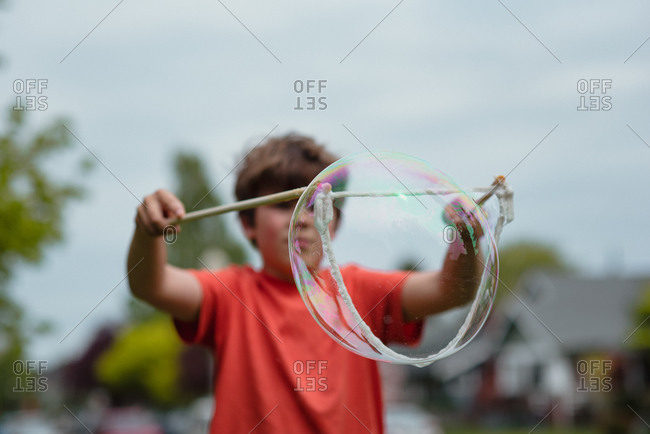 A little boy playing with a large bubble wand