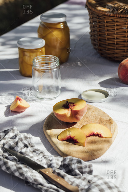Close up of fresh peaches and jars for canning on a garden table