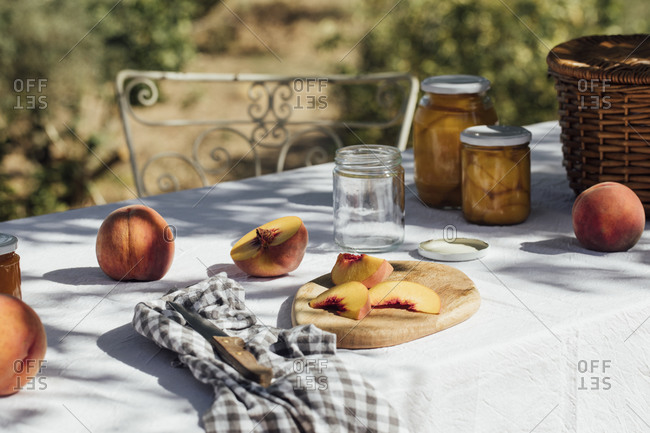 Fresh peaches and jars for canning on a garden table