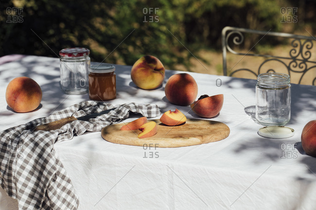 Peaches and jars for canning on a quaint garden table