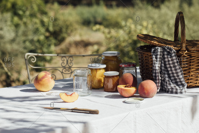 Fresh peaches, jars and a picnic basket on a garden table