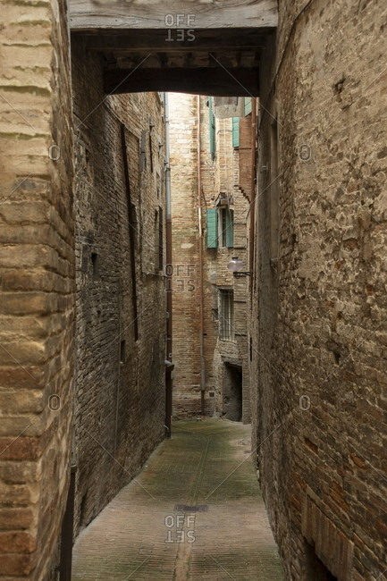 Narrow alleyway surrounded by stone walls in a town in Marche, Italy