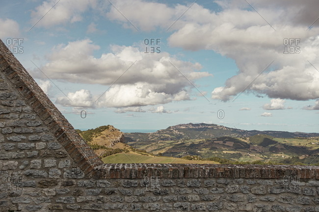 View of countryside over stone wall at the Fortress of San Leo, Marche, Italy