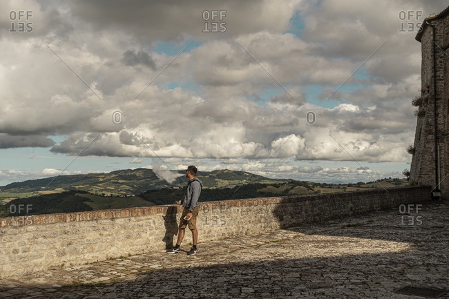 Marche, Italy - August 5, 2020: Tourist overlooking the countryside from the Fortress of San Leo