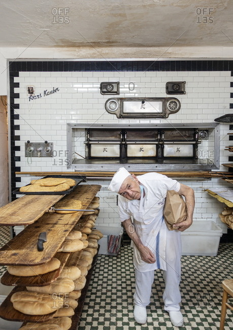 Sassocorvaro, Marche, Italy - August 8, 2020: Old baker working inside the local bakery