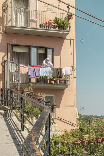 Pennapiedimonte, Abruzzo, Italy - August 10, 2020: Person hanging laundry to dry on balcony