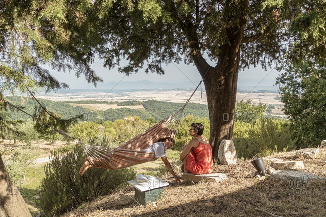 Lajatico, Italy - August 13, 2020: Two people resting under tree and in hammock overlooking the countryside