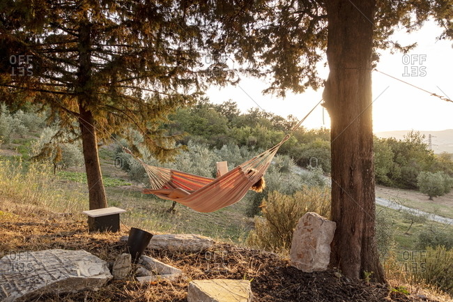 Lajatico, Italy - August 13, 2020: Girl resting and reading a book in hammock overlooking the countryside