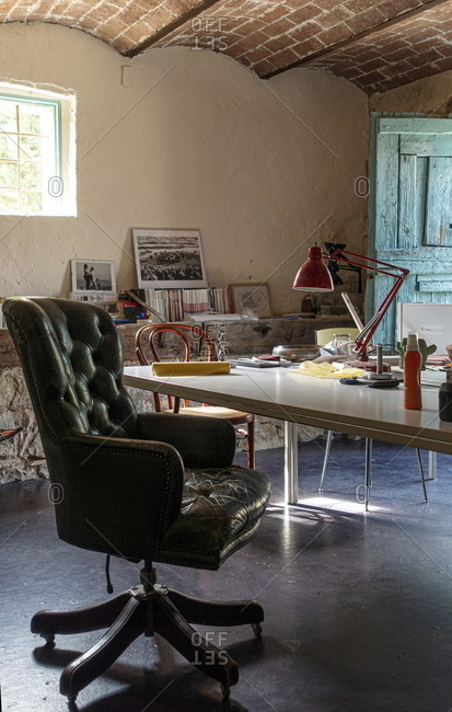 Lajatico, Italy - August 17, 2020: Office interior with arched brick ceiling and leather chair