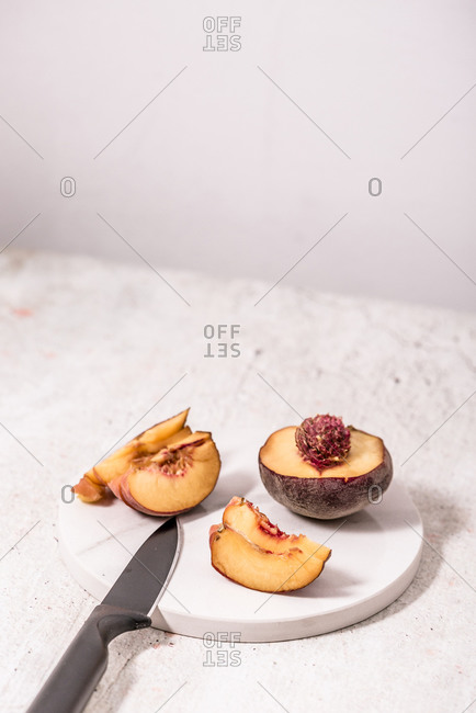 Peaches sliced on cutting stone with knife in front of light background