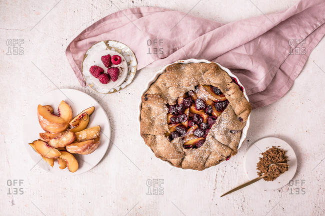 Galette made with fresh yellow peaches, brown sugar and raspberries on light surface