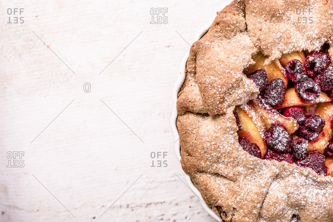 Close up of a galette made with fresh yellow peaches, brown sugar and raspberries
