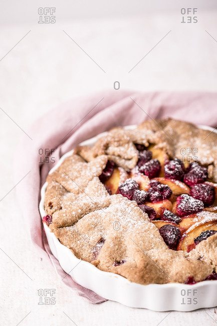 Galette made with fresh yellow peaches, brown sugar and raspberries and sprinkled with sugar