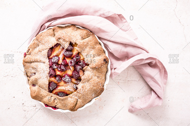 Overhead view of a delicious galette made with fresh yellow peaches, brown sugar and raspberries