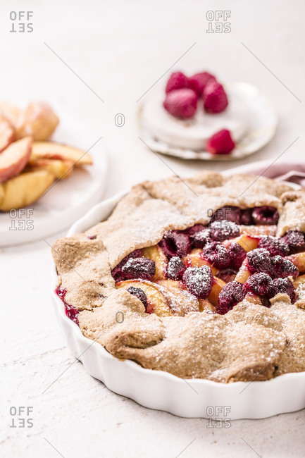Fruit galette made with fresh yellow peaches, brown sugar and raspberries