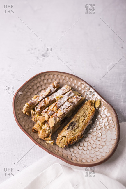 Cut puff pastry with chocolate and marzipan in a dish on light surface