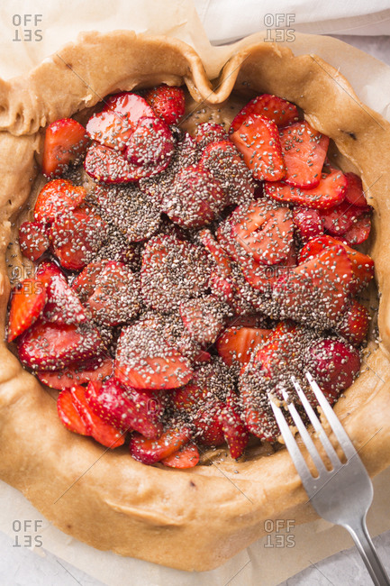 Overhead view of a strawberry galette with vanilla bean and chia seeds being prepared