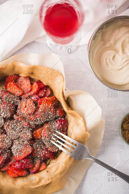 Top view of a strawberry galette with vanilla bean and chia seeds being prepared