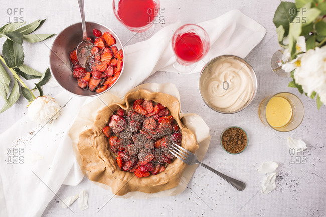 Top view of a strawberry galette with vanilla bean and chia seeds being prepared on light surface