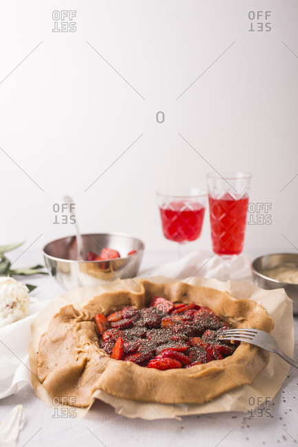 A strawberry galette with vanilla bean and chia seeds in progress with copy space