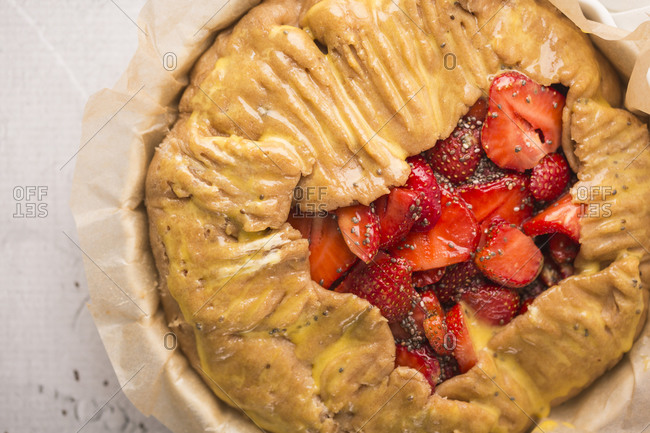 Overhead view of a strawberry galette with vanilla bean and chia seeds ready to be baked