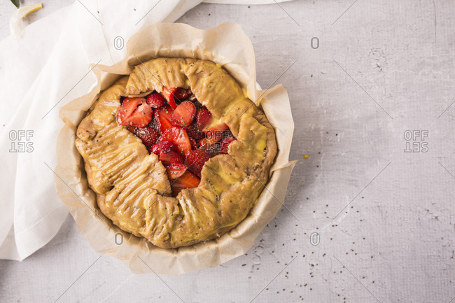 Galette with strawberries, vanilla bean and chia seeds on light surface ready to be baked
