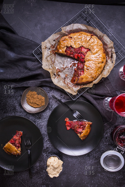 Strawberry galette with vanilla bean and chia seeds on dark background being served