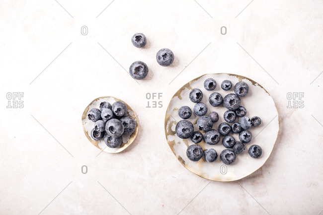 Fresh blueberries in white bowls on light surface