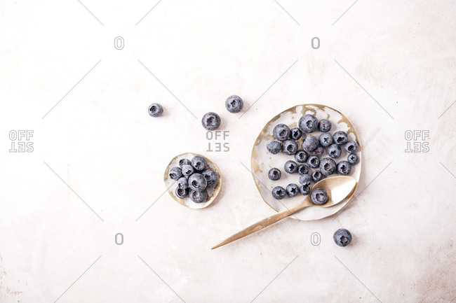 Overhead view of fresh blueberries in white bowls on light surface