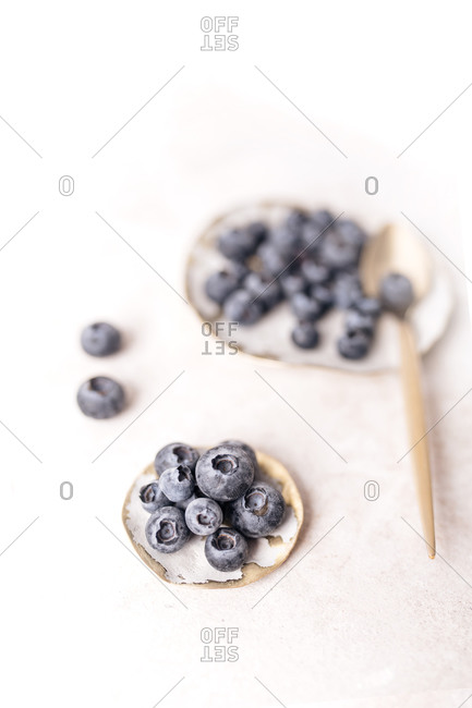Close up of fresh blueberries in white bowls on light surface