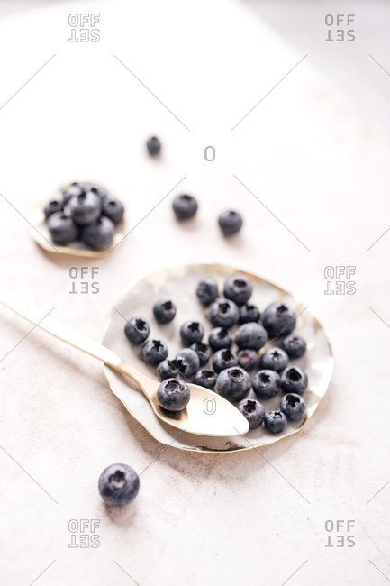 Fresh blueberries in white bowls with spoon on light surface