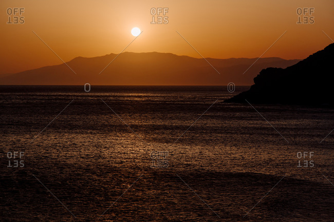 Peaceful scenery of sea and mountain range under sky with amazing orange sundown