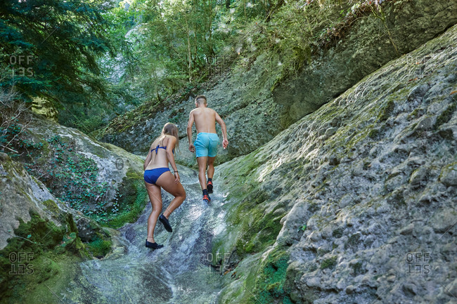 Low angle back view of couple of tourists in swimwear climbing rocky slope in forest during summer holiday