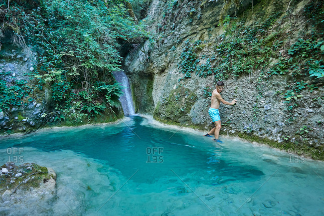 Traveling young man in swimwear crossing river with turquoise water in mountainous area while enjoying summer vacation