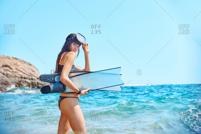 Side view of female diver in goggles and with flippers standing in waving sea and looking over shoulder