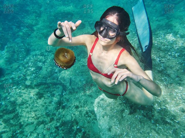 Unrecognizable young woman in diving mask swimming in deep transparent sea water and exploring jellyfish