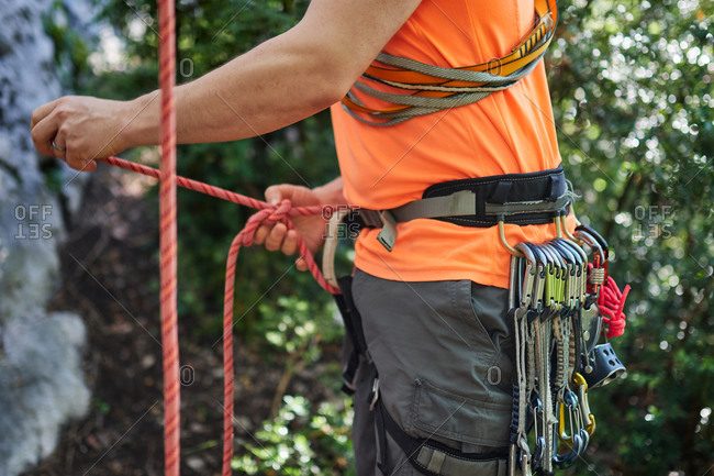 Side view of male climber wearing safety belt with carabiners preparing for climbing rock in forest