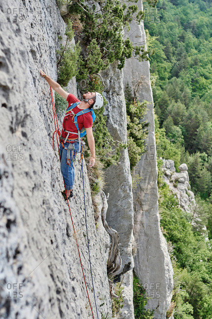 Side view of mountaineer in safety equipment climbing steep rock during summer vacation